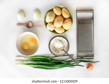 Potato pancakes ingredients. Potatoes, green onions, eggs, flour and grater. Cooking. Healthy food layout. Isolated tasty raw vegetables on white background. Vegetarian receipes. Food styling photo