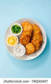 Potato pancakes, latkes or boxty and sauces from sour cream, yogurt, apple sauce and finely chopped green onion isolated on a blue background