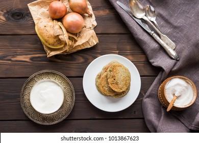 potato pancakes on white plate with vintage cutlery rustic wooden table top view. National Belarusian Ukrainian dish draniki sour cream salt onion potato ingredients fried golden flapjacks.