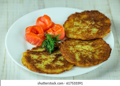 Potato pancakes on a white plate with slices of salmon
