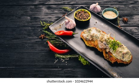 Potato pancakes with pork. Hot appetizers. Top view. On a black wooden background. Copy space.