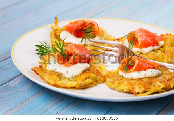 Potato Pancakes With Salmon. Vegetable fritters with fish. Latkes on a plate