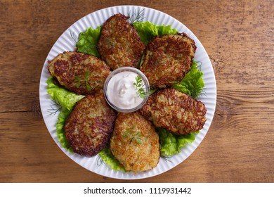 Potato pancakes with sour cream or yogurt. Vegetable fritters, latkes, draniki. View from above, top studio shot