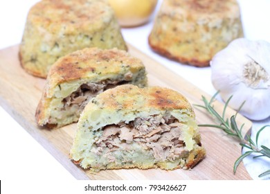 Potato pie with tuna on wooden chopping board
