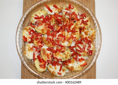 Potato pizza with red and black pepper, cheese, basil and thyme in round baking glass on wood texture.