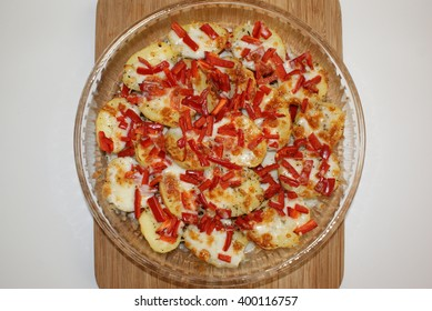Potato pizza with red pepper, cheese, basil and thyme in round glass on wood.