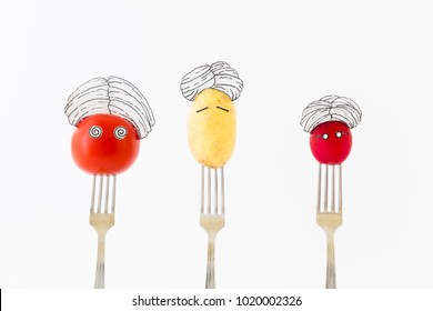 Potato, red tomato and radish on white background with turban sitting as fakir on top of silver forks representing indian food.