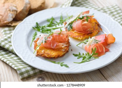 Potato rosti with South Tyrolean bacon, parmesan cheese and rocket salad served on a white plate