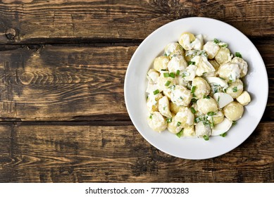 Potato salad with eggs and green onion on white plate over wooden background with copy space. Top view, flat lay food