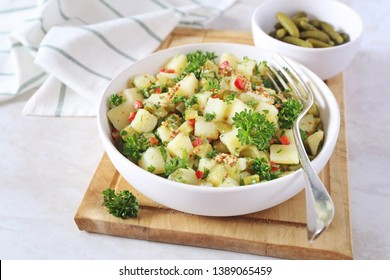 Potato salad with pickled cucumbers and parsley, mustard sauce on light background