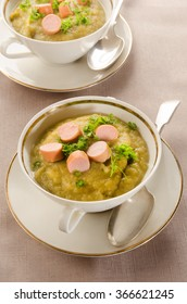 potato soup with sliced vienna sausages and parsley in a bowl