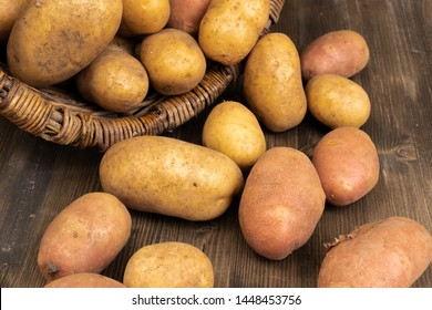 Potato tubers lie on a dark gray wooden board near a wicker wooden basket that has fallen on its side.