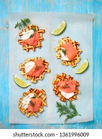 potato waffles with salmon, cream cheese on a blue wooden background. view from above