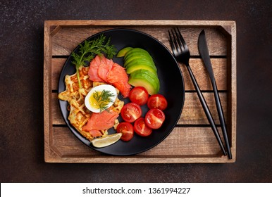 potato waffles with salmon, egg, avocado and tomatoes on a black plate on a dark background. view from above.