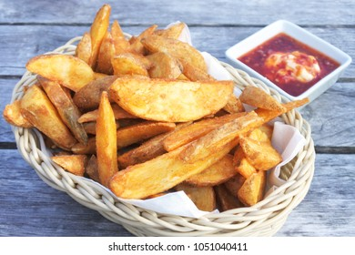 potato wedges served in a basket with hot chilli sauce on a table. Food background and texture. Copy space