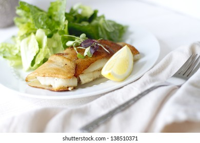 Potato wrapped cod with a lemon wedge.