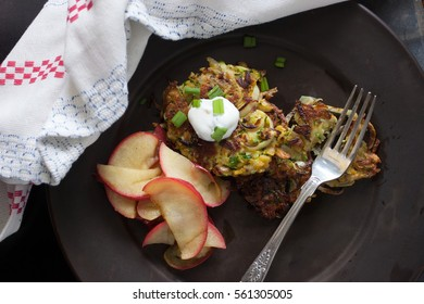 Potato zucchini latkes with green onion, a dollop of sour cream, and sliced apples