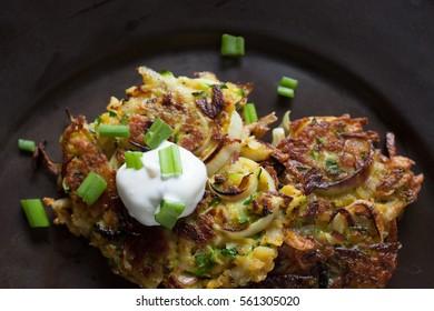 Potato zucchini latkes with green onion and a dollop of sour cream