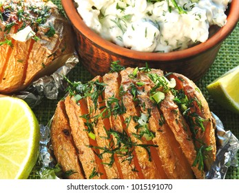 Potatoes baked in their skins with herbs and lime slices. Baked potatoes and lime.