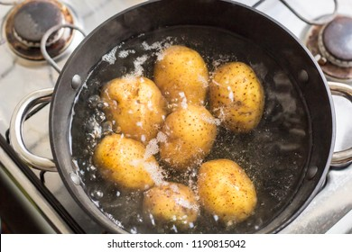 Potatoes boiling in a saucepan on a gas hob.