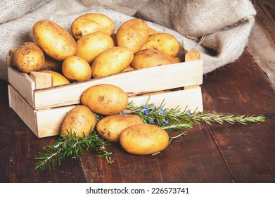 Potatoes in a box on a rustic wooden table