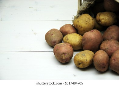 Potatoes in box on a wooden table . Free space for text. Top view