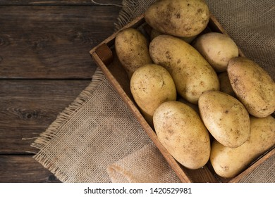Potatoes in a box on a wooden table. Rustic style