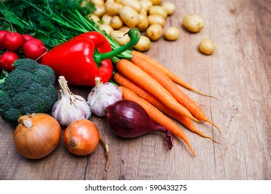 Potatoes with carrot, garlic and pepper. Red radish, brocoli and raw new potato. Onion. Fresh natural vegetables. Organic bio food. On wooden table.
