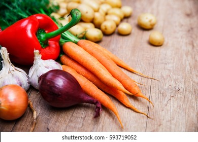 Potatoes with carrot, garlic and pepper. Red radish, onion and raw new potato. Fresh natural vegetables. Organic bio food. On wooden table.