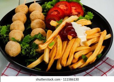 Potatoes fries with meatballs and tomato salad on a black plate