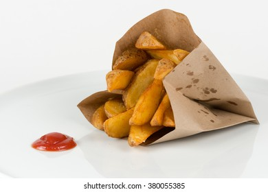 Potatoes fries in a paper bag with ketchup isolated on white