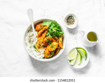Potatoes and green beans curry sauce with rice and cilantro. Indian vegetarian healthy food on grey background, top view