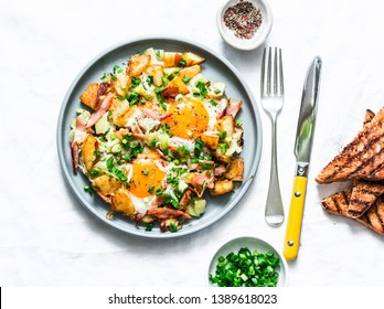 Potatoes, ham, eggs breakfast hash on a light background, top view. Delicious, nutritious breakfast, snack