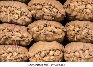 Potatoes in hessian stacked sacks await sale at an Asian wholesale market.