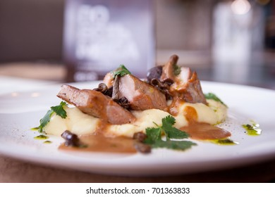 Potatoes and meat on a plate on a wooden table