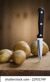 Potatoes on a cutting board - Main focus on knife.