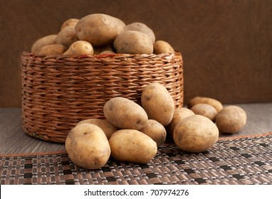 Potatoes on a dark background. Many potato tubers in a wicker basket. Potatoes in a wicker box and on a table. Potatoes are scattered around the basket.