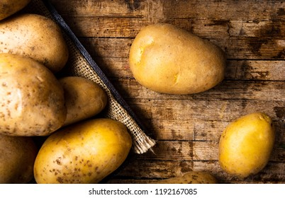 Potatoes on wooden background closeup