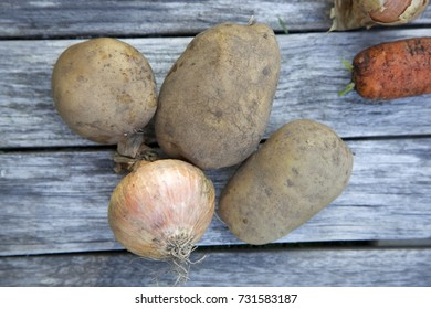 Potatoes, onion, carrot. Unwashed. Grey wooden background. Daylight