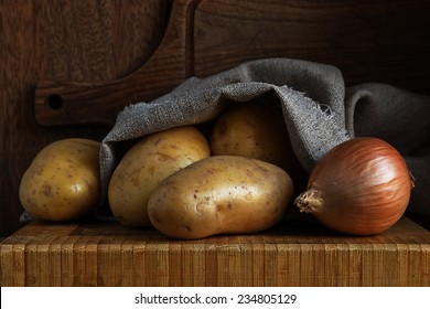 potatoes and onion, spill out canvas bag on a wooden board
