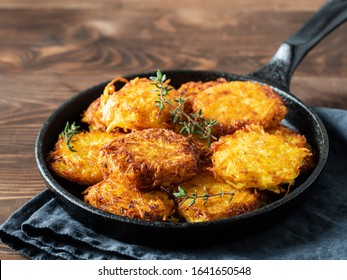Potatoes pancakes latkes, flapjacks, hash brown or potato vada on brown wooden table. Copy space for text.