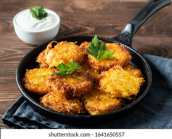 Potatoes pancakes latkes, flapjacks, hash brown or potato vada with white greek yoghurt or sour cream on brown wooden table. Copy space for text.