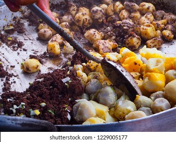 Potatoes and pig blood curd fried in pan, Ecuadorian food, selective focus, top view