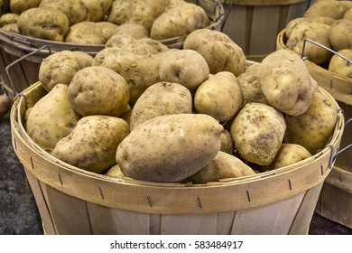 Potatoes, piled into a natural wood basket, are on sale at a produce market.