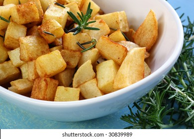 Potatoes roasted with rosemary, in stylish white bowl.  Close-up view.