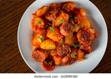 Potatoes stew with pork sausages and herbs - top view
