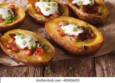 Potatoes stuffed with cheese, bacon and sour cream close-up on the table. horizontal, rustic