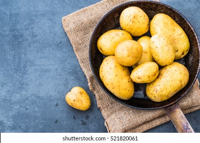 Potatoes top view on rustic dark background copy space.