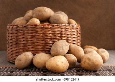 A lot of potatoes. A lot of potatoes in a wicker basket. Potato tubers in wicker ware and scattered on the table. Harvest of potatoes. Vegetables for a healthy diet.