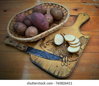 Potatoes in a wicker basket. Sliced potatoes with a knife on the board.